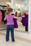 La pequeña muchacha linda cerca de un espejo intenta encendido la ropa imagenes de archivo