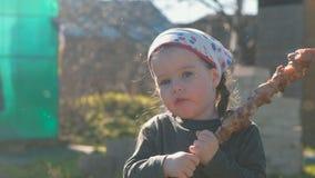 La pequeña muchacha linda come el shashlik de la barbacoa en un pincho almacen de video