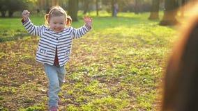 La pequeña muchacha linda con dos colas de caballo está corriendo a la madre joven y la está abrazando familia feliz que pasa el  metrajes