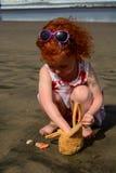 La pequeña muchacha linda del pelirrojo ha encontrado cáscaras en la playa de Bali imagen de archivo libre de regalías