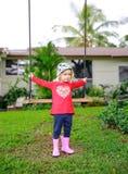 La pequeña muchacha linda del trastorno que balancea a la niña linda en una camisa roja está lista para swingwooden el oscilación Fotos de archivo