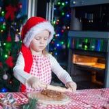 La pequeña muchacha linda en el sombrero de Papá Noel cuece el pan de jengibre Imagenes de archivo