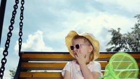 La pequeña muchacha linda en gafas de sol balancea en una oscilación contra el cielo azul almacen de video