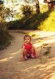La pequeña muchacha linda en vestido rojo se está sentando en el camino Imagenes de archivo