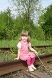 La pequeña muchacha linda en vestido rosado con el palillo se sienta en ferrocarril viejo en Fotografía de archivo