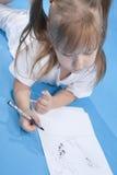 La pequeña muchacha linda está bosquejando Imagenes de archivo