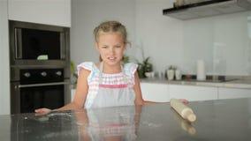 La pequeña muchacha linda está cocinando en cocina Divertirse mientras que hace las tortas y las galletas Sonriendo y mirando la  metrajes