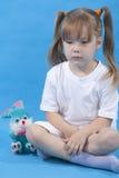 La pequeña muchacha linda está presentando en fondo azul Imagenes de archivo