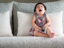 La pequeña muchacha linda feliz está leyendo el libro en el sofá blanco Ed imagen de archivo libre de regalías