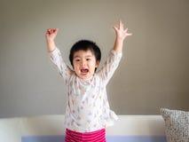 La pequeña muchacha linda feliz que ríe y aumenta la mano para arriba en el sof fotos de archivo