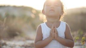 La pequeña muchacha linda medita al aire libre en la puesta del sol con la luz natural hermosa metrajes