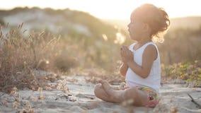 La pequeña muchacha linda medita al aire libre en la puesta del sol con la luz natural hermosa almacen de video