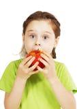 La pequeña muchacha linda muerde una manzana roja grande con apetito Fotos de archivo