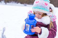 La pequeña muchacha linda se calienta las manos en vela en azul Fotografía de archivo