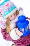 La pequeña muchacha linda se calienta las manos en vela en azul Fotografía de archivo libre de regalías