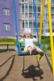 La pequeña muchacha linda se sienta en el oscilación Fotos de archivo libres de regalías