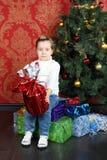 La pequeña muchacha linda se sienta en el regalo en piso cerca del árbol de navidad Imágenes de archivo libres de regalías