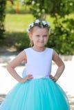 La pequeña muchacha linda se vistió en vestido azul y blanco con una guirnalda de las flores artificiales en su cabeza, niño en u Fotos de archivo