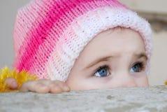 La pequeña muchacha mira hacia fuera detrás de un parapeto Imagen de archivo
