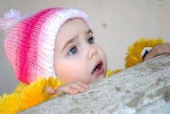 La pequeña muchacha mira hacia fuera detrás de un parapeto Imagen de archivo libre de regalías