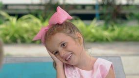 La pequeña muchacha pone la cabeza a mano y risas cerca de piscina almacen de video