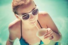 La pequeña muchacha rubia bebe el cóctel en una piscina Imágenes de archivo libres de regalías