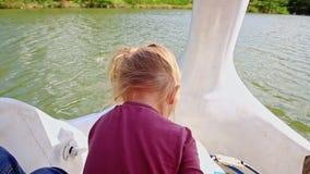 La pequeña muchacha rubia del primer da vuelta a pedales de la bici del agua con la mano almacen de metraje de vídeo