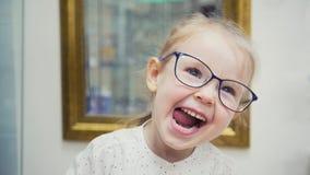 La pequeña muchacha rubia en el pasillo de la clínica de la oftalmología tiene la diversión y juegos con los vidrios Imágenes de archivo libres de regalías