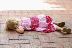 La pequeña muchacha rubia en vestido rosado miente en parque Imagenes de archivo