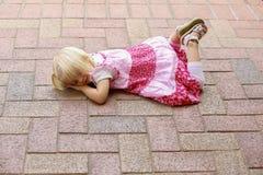 La pequeña muchacha rubia en vestido rosado miente en parque Fotografía de archivo libre de regalías
