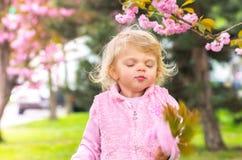 La pequeña muchacha rubia encantadora la cerró los ojos con placer Fotografía de archivo