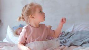 La pequeña muchacha rubia encantadora juega con el baloon en el vestido rosado que se sienta en cama almacen de metraje de vídeo