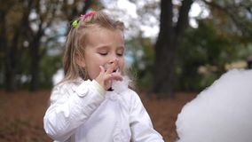 La pequeña muchacha rubia está comiendo el caramelo de algodón dulce en el parque de la ciudad Niña hermosa que come la caramelo- almacen de metraje de vídeo