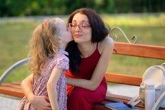 La pequeña muchacha rubia linda está besando a su madre morena joven en Eyesglasses y el vestido rojo que se sientan en el banco  Fotos de archivo libres de regalías