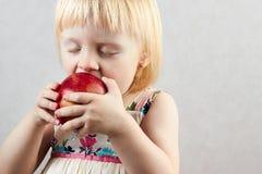 La pequeña muchacha rubia muerde la manzana roja grande Fotos de archivo