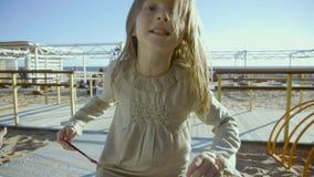 La pequeña muchacha rubia salta hilarantemente en un patio en una costa en el slo-MES metrajes