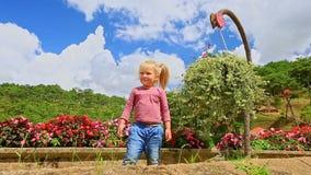 La pequeña muchacha rubia sonríe mano de las ondas de los gritos por el primer de las flores almacen de video