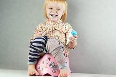 La pequeña muchacha se sienta en un potty imagen de archivo libre de regalías