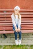 La pequeña muchacha sonriente en un casquillo se sienta en banco foto de archivo