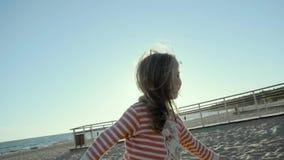 La pequeña muchacha sonriente se coloca, corre, y salta en una playa del mar, en la puesta del sol en el slo-MES metrajes