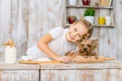 La pequeña muchacha sonriente se está inclinando abajo a su animal doméstico Fotos de archivo