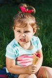 La pequeña muchacha sostiene una taza de la galleta con la frambuesa Foto de archivo