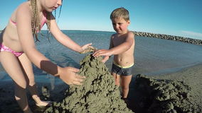 La pequeña muchacha y el muchacho hermosos que construyen la arena se escudan metrajes