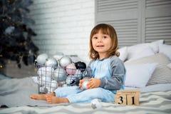 La pequeña niña linda es 2 años que se sientan cerca del árbol de navidad y que miran el calendario el 31 de diciembre Imagen de archivo