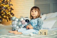 La pequeña niña linda es 2 años que se sientan cerca del árbol de navidad y que miran el calendario el 31 de diciembre Foto de archivo