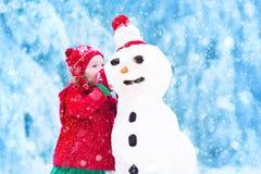 La pequeña niña pequeña divertida en un rojo hizo punto el sombrero nórdico y la capa caliente que jugaban con una nieve imagen de archivo