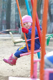 La pequeña niña pequeña en guardapolvo caliente azul marino se está sentando en el oscilación de los patios Fotografía de archivo