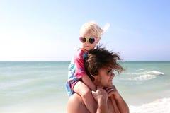 La pequeña niña pequeña que se sienta en el ` s del padre lleva a hombros en la playa por el th fotos de archivo libres de regalías