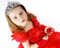 La pequeña princesa linda se vistió en rojo aislada en el fondo blanco Fotografía de archivo