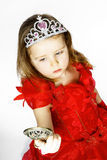 La pequeña princesa linda se vistió en rojo aislada en el fondo blanco Foto de archivo
